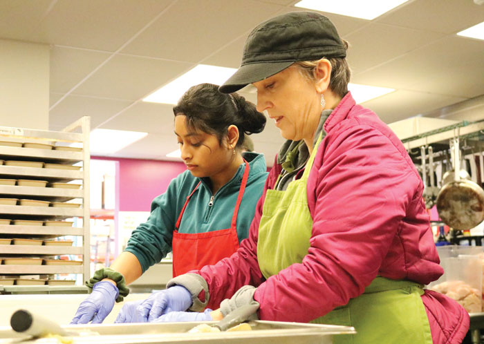 Junior Navya Mangipudi and history teacher Abigail Hundley work on service day. Some students are looking to change service requirements.