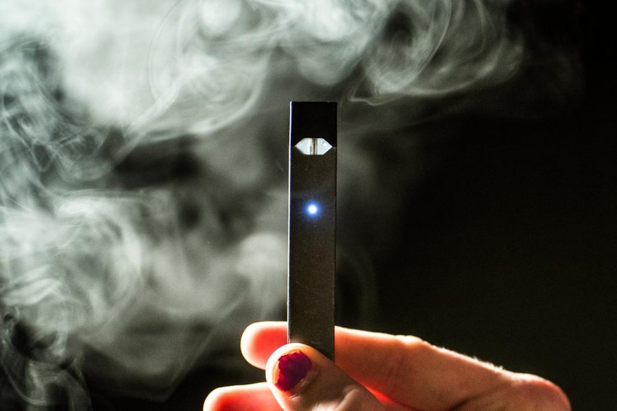 A teenager holds a vaping device. Health concerns have caused new reforms in how e-cigarettes are sold.