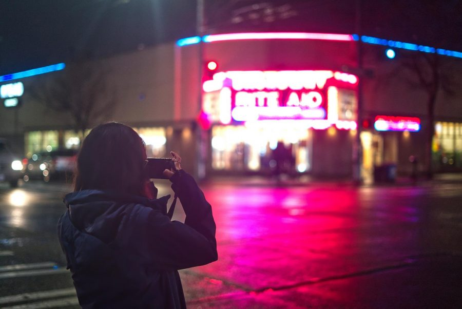 Junior Keila Santos takes a photo of the front of a Rite Aid.