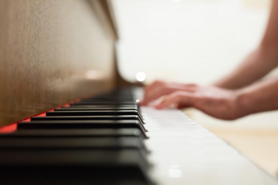 A side profile of a person playing a piano. (Negative Space/Pexels)
