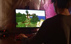 A man playing Minecraft in a dark room. (Alexander Kovalev/Pexels)