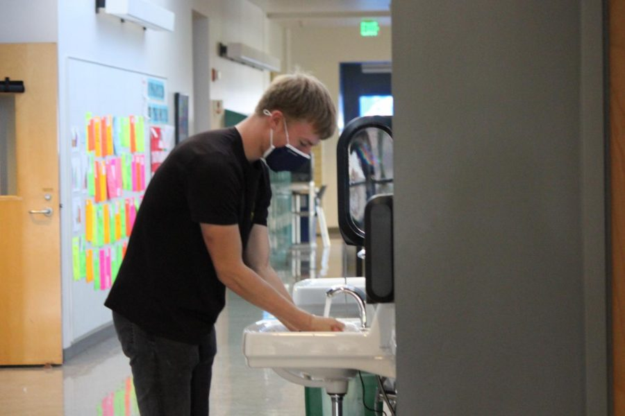 Henry Buscher washes his hands in the new sinks in the Classroom Building.