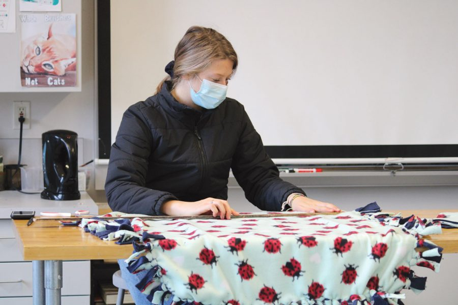 Sophomore Katharine Jackson measures the length of her cloth while making a blanket for the homeless on November 13th's Service Day.