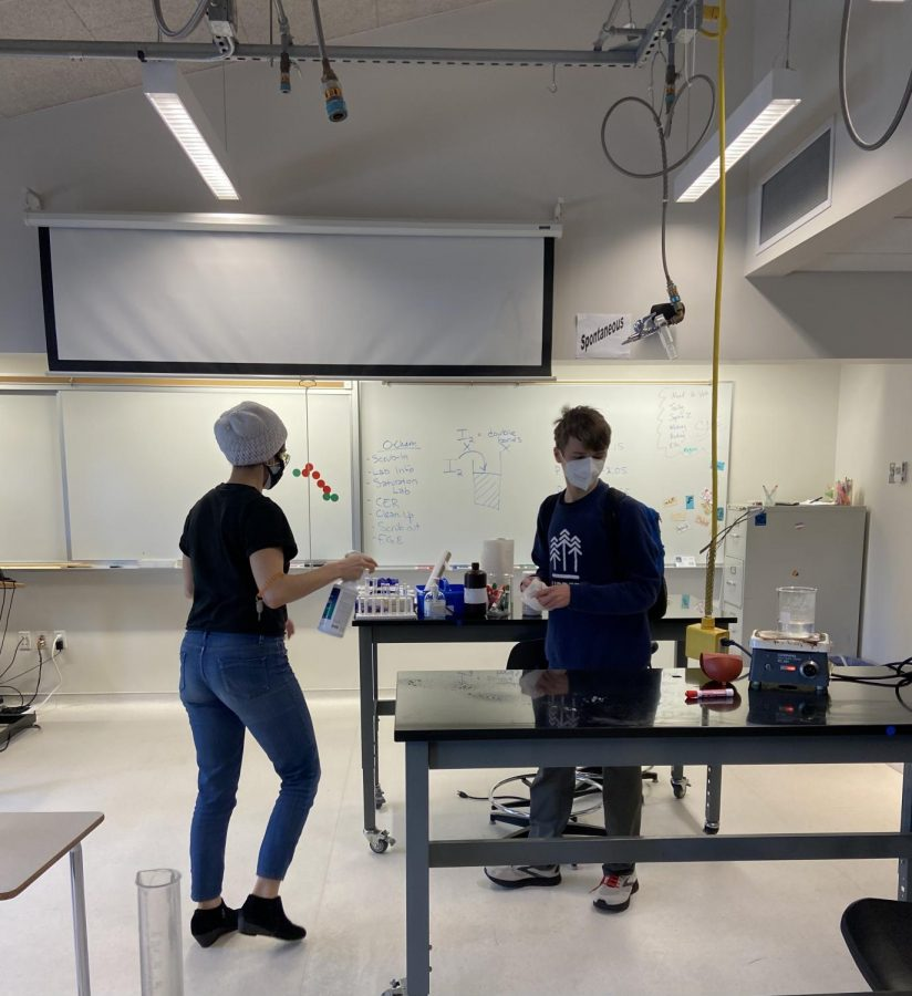 Chemistry teacher Mikayla Patella-Buckley and Junior Andrew Bell wipe down tables at the beginning of class.