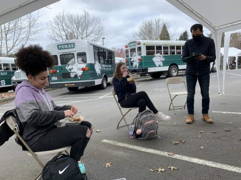 Sophomres Sydney Goitia-Doran and Delia Rossi share a laugh during lunch on campus while Director of Upper School Joel Sohn takes attendance. Students eat socially distanced outside in the faculty parking lot.